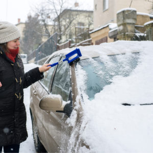Woman cleans snow from her car