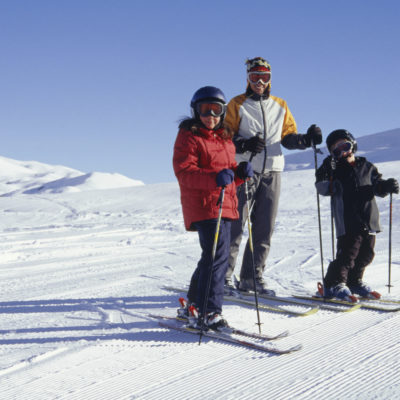Father with daughter and son on ski slope