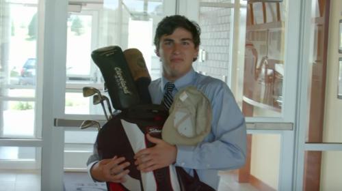 man holding golf clubs