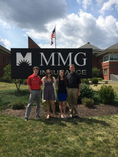 MMG interns posing by sign