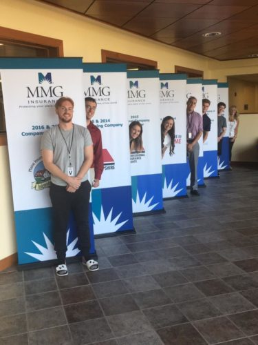 MMG interns posing next to banners