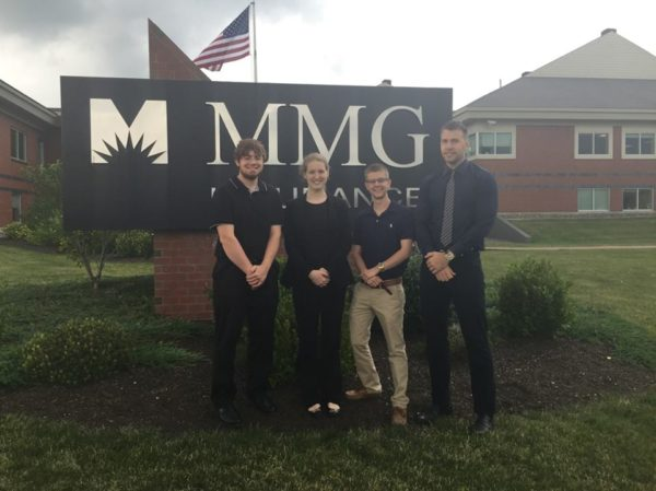 Interns standing next to MMG sign